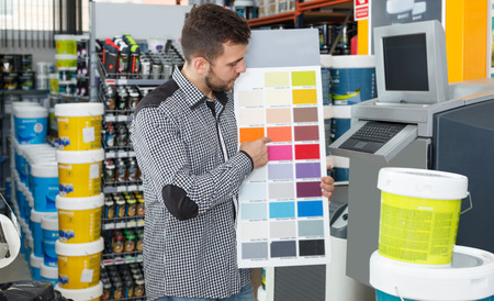 Cheerful young male looking samples of color at palette in household store