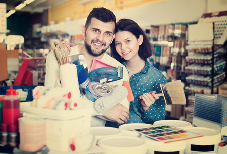 Cheerful  couple purchasing tools for house improvements in paint supplies store Фото со стока - 120130629