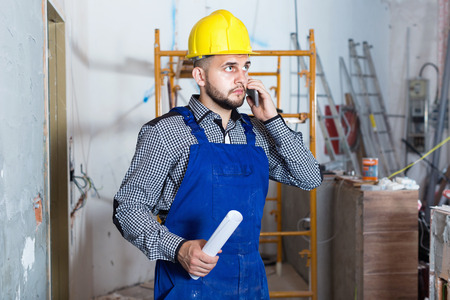 Diligent serious male worker is clarifying details of work from client.