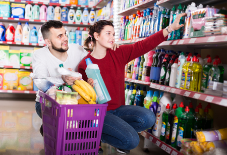 two attentive adult people in good spirits selecting detergents оn the shelves in the store