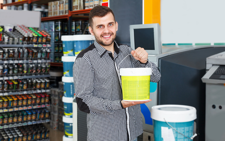 Young man standing near shelves and holding  bucket of paint in household shop 写真素材