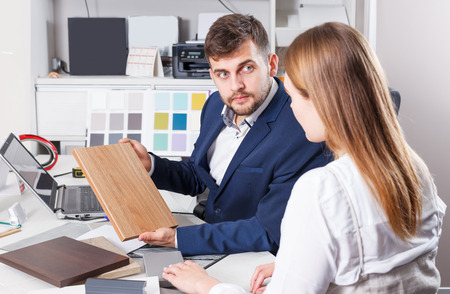 Positive girl planning new furniture in her house in furniture salon