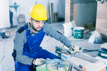 Serious male worker is preparing for repair in the room at object