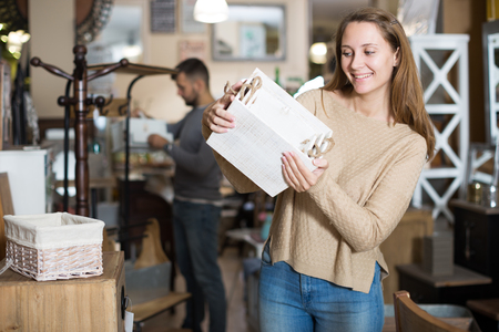 Attractive girl with boyfriend choosing home decor elements in furnishings store