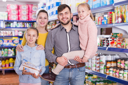 Portrait of cheerful family with two daughters in food store Stok Fotoğraf