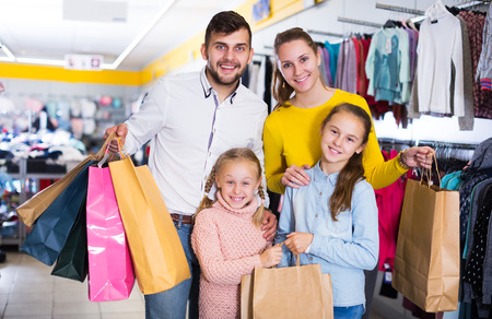 friendly young family of four with shopping bags in clothing shop 스톡 콘텐츠