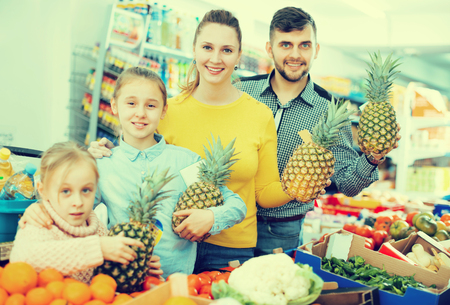 Cheerful family with pineapples during family shopping in vegetable department of grocery store Imagens