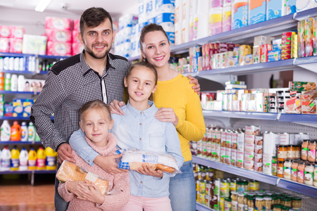 Happy spouses with two little girls during family shopping in grocery store