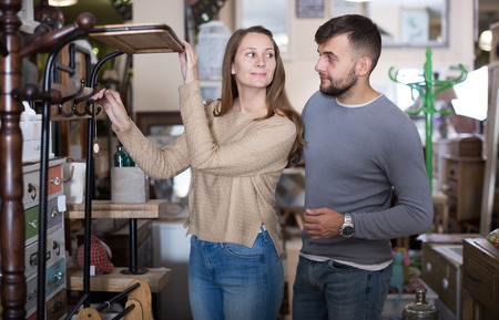 Portrait of happy couple choosing hallstand in furnishings store