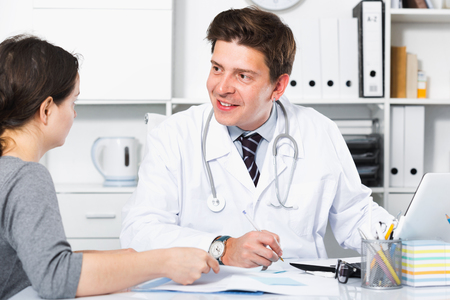 Happy positive doctor speaking with client in the medical center