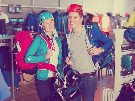 Young girl and guy are choosing travel gear in sports shop