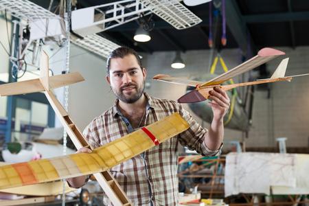 Entusiasta de los aviones masculino alegre sosteniendo modelos de aviones deportivos en el taller Foto de archivo