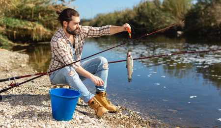 Positive fisherman holding catch freshwater fish in hands