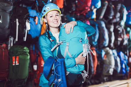 cheerful girl chooses a backpack for camping from assortment in the sports shop Stock Photo