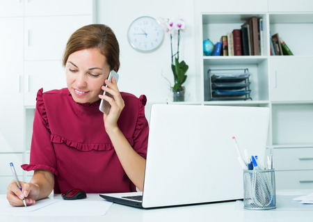 Smiling woman taking notes while talking on mobile phone at company office