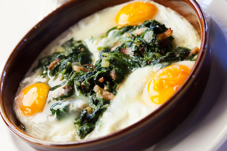 Traditional Catalan fried eggs with spinach, raisins and ham served in clay bowl Stock Photo