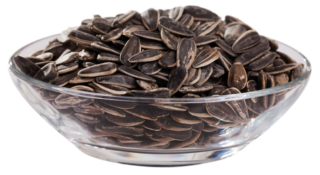 Glass bowl with sunflower seeds in hulls. Popular snack food. Isolated over white background