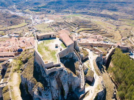 Aerial view of tiled housetops and castle in medieval Morella, Spain