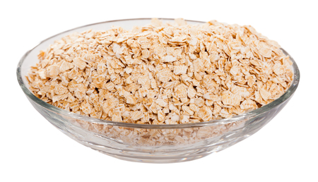 Oat flakes in oval glass bowl. Concept of healthy food. Isolated over white background
