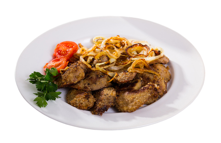 Fried rabbit liver served on white plate with grilled onion and cherry tomatoes. Isolated over white background