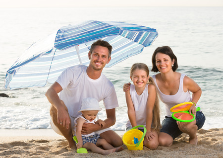 smiling parents with two kids sitting under sun umbrella with sand toys on beach