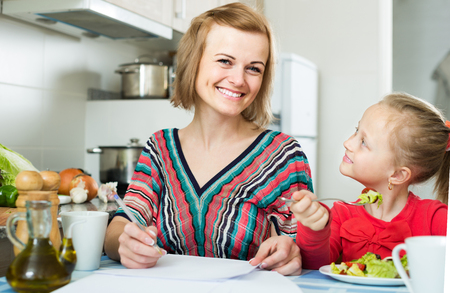 Successful russian woman and her daughter working with papers from home
