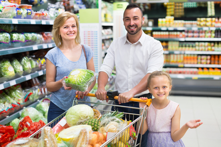Smiling parents with child choosing lettuce in supermarket. Focus on girl Reklamní fotografie