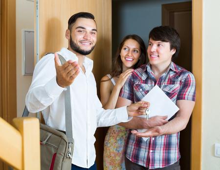 vastgoedverkoper die nieuwe flat toont aan jong gezin Stockfoto