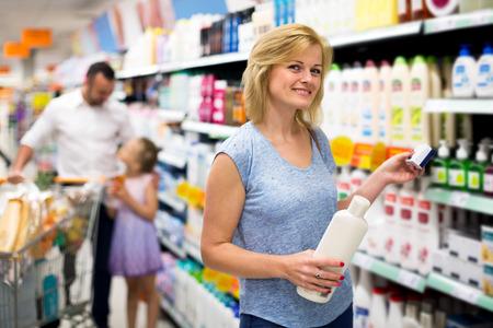 Cheerful woman customer choosing shampoo in cosmetics department Banco de Imagens