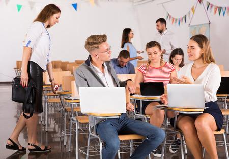 Glimlachende volwassen studenten communiceren tijdens pauze tussen lezingen in auditorium