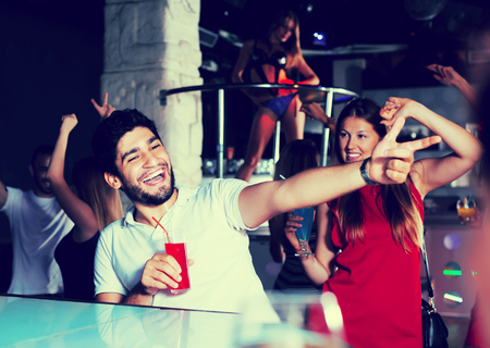 Cheerful men and women joying and dancing with drinks on party in the nightclub Stok Fotoğraf