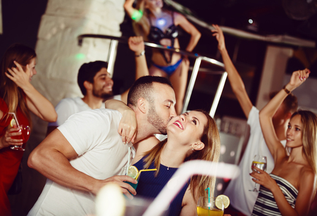 positive couple dancing and hugging on party in the club
