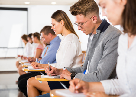 Vista lateral del grupo de estudiantes trabajando en una conferencia en el aula, tomando notas Foto de archivo