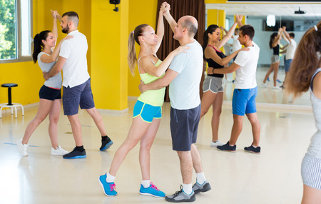 Men and women are dancing waltz in pairs in dance class.