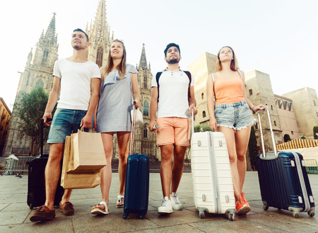 portrait of four happy young people tourists friends walking in town together in summer day