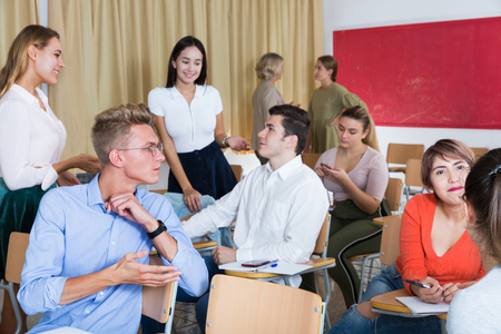 Smiling adult students communicating during recess between lectures in auditorium