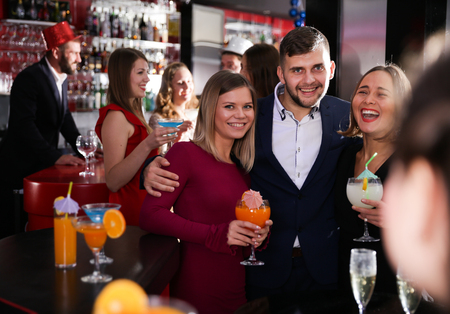 Cheerful guy with two girls partying in bar, dancing and toasting drinks