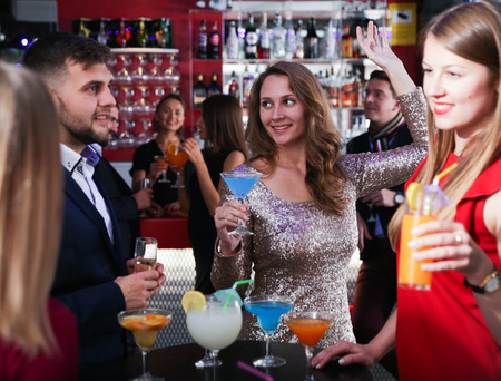 Young attractive woman with cocktails having fun with friends at nightclub