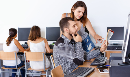 Young efficient positive students reading textbook together while studying in university computer class