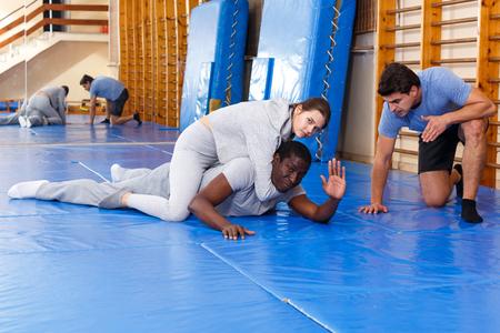 Hombre y mujer en ropa deportiva ejercitando técnicas de autoprotección en pareja en el gimnasio