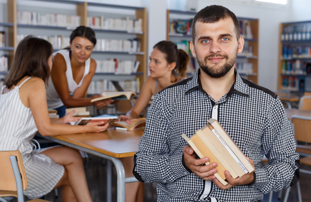 Portrait of confident male student sitting with pile of books in university library on background with working coursemates Stock Photo