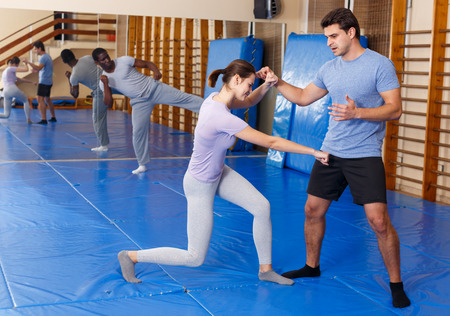 Woman and man practicing self defense techniques in gym Stockfoto