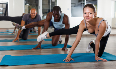 Group of smiling young  women and males doing stretching workout at gym Stock Photo