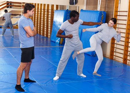 Junge Leute üben in Paar-Selbstverteidigungsbewegungen unter Aufsicht eines männlichen Trainers