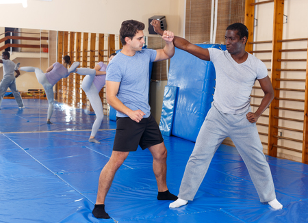Two young men practicing self defense techniques in sports club