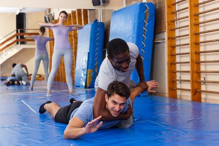 Dos hombres jóvenes practicando técnicas de autodefensa en el club deportivo