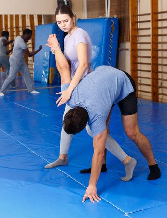Frau und Mann üben Selbstverteidigungstechniken im Fitnessstudio practicing Standard-Bild