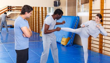 Jóvenes practicando en pareja movimientos de autodefensa con la supervisión de un entrenador masculino