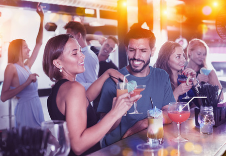 Portrait of cheerful positive smiling females and males having fun in the bar