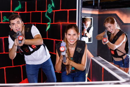 First cheerful person view of young people aiming from laser gun in dark laser tag game room Standard-Bild